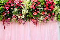 exotic flowers arrangement over pink fabric, flowers background.