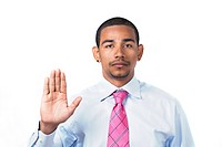 Hispanic man taking an oath or pledge with right hand raised and serious expression