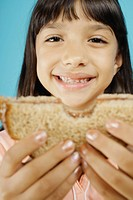 Young girl holding sandwich