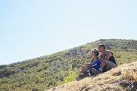 African American couple sitting on hill outdoors