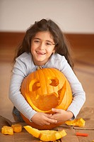 Portrait of girl hugging jack o´lantern