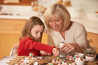 Mother and daughter decorating homemade gingerbread cookies