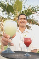 Hispanic male waiter with a tray of drinks