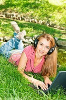 Beautiful young student with headphones using computer outdoors.