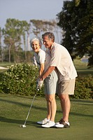 Senior man helping wife with golf swing
