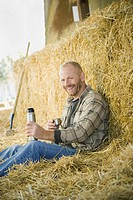 Man sitting in hay drinking from thermos