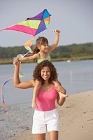 Hispanic mother and daughter flying kite on beach