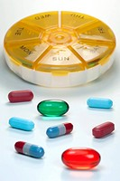 Macro closeup of colored pills and medication, daily dated pill box in background.