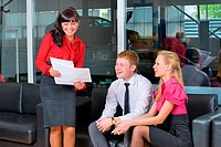 Young family in car service office talking with manager