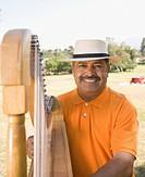 Middle_aged Hispanic man playing harp outdoors
