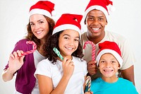 happy multiracial family wearing Christmas hats and holding candy cane