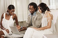 Multi_ethnic friends looking at laptop