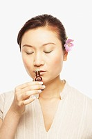 Asian woman smelling aromatherapy bottle