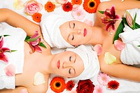 Two girls relaxing in a wellness set_up seen from above, horizontally aligned, with some flowers, closed eyes