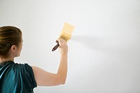 Woman painting white wall with bright yellow paint, concept photography