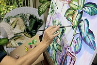 beautiful blond artist in her fifties painting a still life in her studio