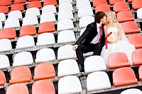 Bride and groom on the sport stadium seats