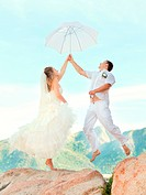 Bride and groom jumping on a rock with umbrella