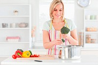 Woman cooking broccoli in the kitchen