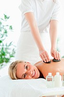 Blonde woman experiencing a stone therapy in a wellness center