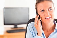 Smiling working woman speaking on the phone in her office