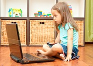 little girl with laptop sitting on the floor in the middle of the room