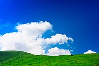 Blue cloudy sky and green spring hill
