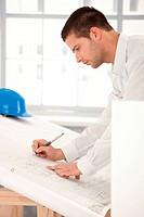 Young goodlooking engineer making plans on drawing table.