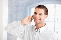 Handsome young man talking on mobile phone, smiling.