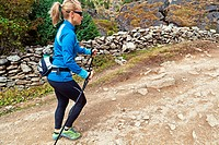 Young woman nordic walking in Himalaya Mountains in Nepal, motion blur