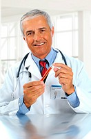 Middle aged doctor holding as test tube with red liquid in modern medical facility. Man is wearing a lab coat, blue shirt and tie and stethoscope. Ver...