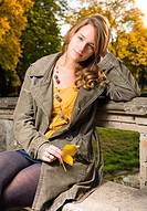 Beautiful young fashionable woman posing in autumn park.