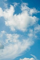Natural shot of a blue sky with white fluffy clouds. Portrait vertical orientation.