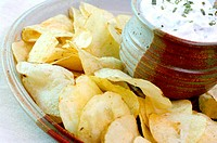 Slanted close up view of a place of potato chips and sour cream dip.