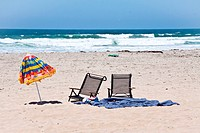 Shot of two chairs and umbrella at a tropical beach.