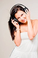 Beautiful smiling brunette in white dress, with flowing hair, enjoying music in headphones.