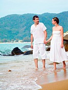 outdoor portrait of young romantic couple in white cotton clothes on beach of Phuket island, Thailand