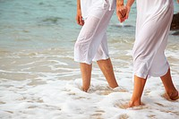 body part outdoor portrait of couple´s legs in white cotton clothes walking along coastal strip of Phuket island, Thailand