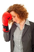 Profile of loser business woman holding hand in boxing glove to head against white background