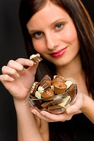 Chocolate _ portrait of young woman hold candy in bowl