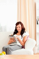 Charming woman holding a tablet in her livingroom