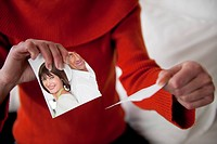 Woman Tearing Photograph of Her Relationship