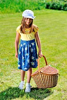 Girl with picnic basket on a meadow