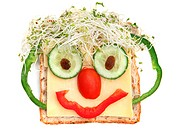 Face on bread, made from cheese, sprouts, capsicums, tomato, cucumber and sultanas. Healthy fun snacking.
