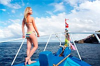 outdoor portrait of beautiful young blonde woman in bikini on yacht