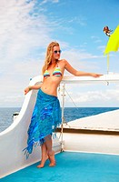 outdoor portrait of beautiful young blonde woman in bikini and sunglasses and pareo on yacht´s deck