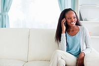 Smiling woman phoning on sofa
