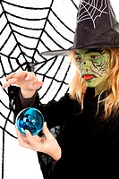 Portrait of green Halloween witch girl holding big blue marble