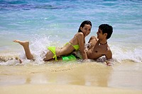 couple playing at the water´s edge on a hawaii beach