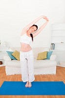 Cute red_haired woman stretching in the living room in her appartment